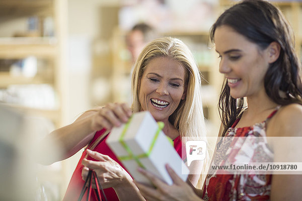 Two happy women with gift box in shop
