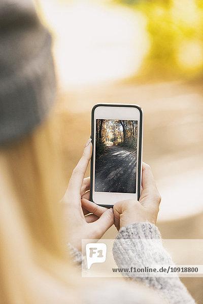 Teenagermädchen macht Handyfoto auf Waldweg