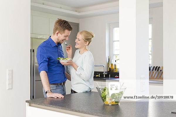 Glückliches Paar in der Küche mit Salat