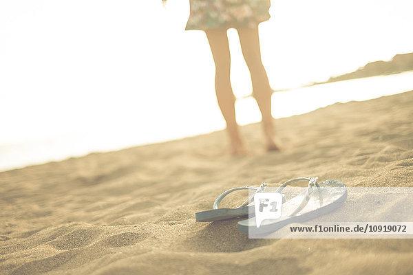 Spanien  Teneriffa  junge Frau am Strand stehend  Flip-Flops im Vordergrund