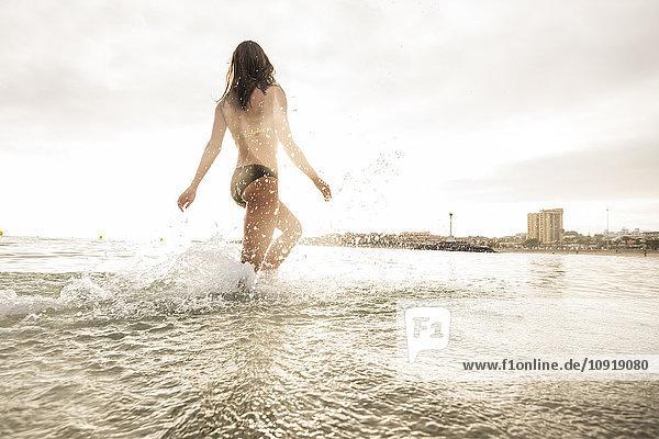 Spanien  Tenerifa  junge Frau  die gegen die Sonne ins Wasser läuft