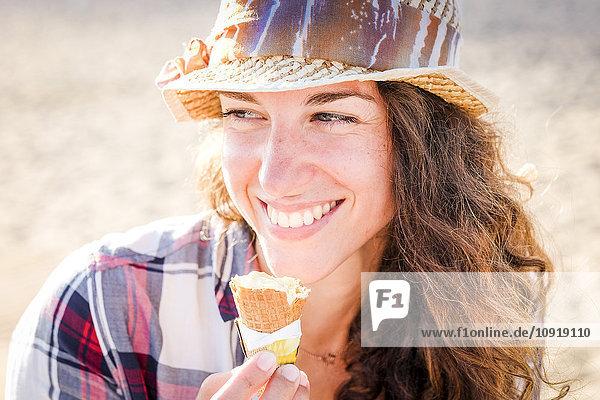 Junge Frau beim Eis essen am Strand