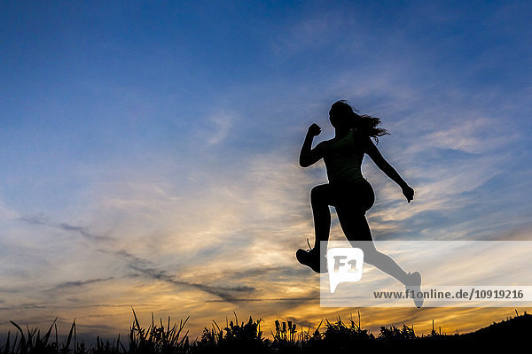 Silhouette der Joggerin bei Sonnenuntergang