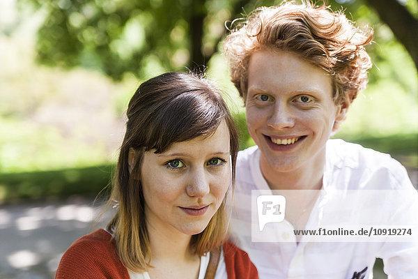 Porträt einer jungen Frau mit lächelndem Freund im Hintergrund