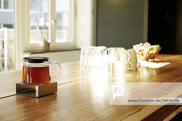 Teekanne auf Teekanne wärmer auf Tischplatte im modernen Büro