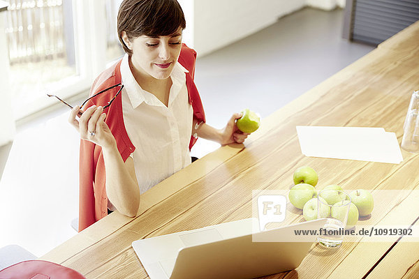 Frau in einer modernen Kantine beim Apfelessen