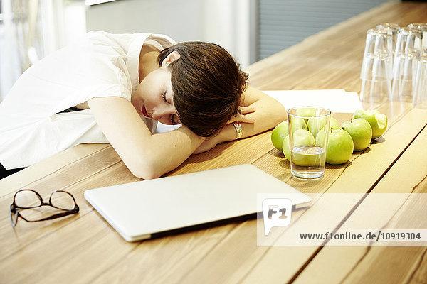 Frau schlafend am Tisch in der Kantine eines modernen Büros
