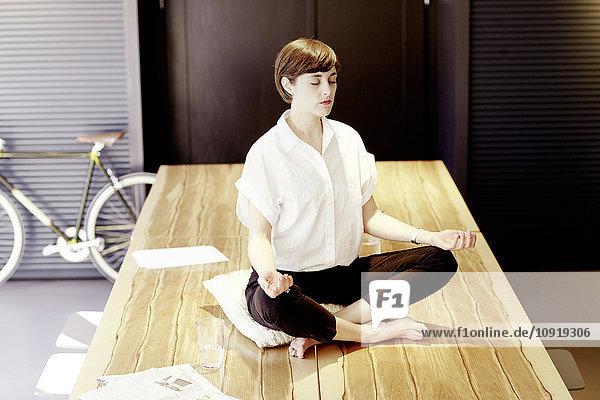 Frau praktiziert Yoga auf Holztisch