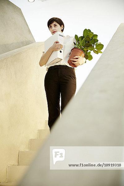 Frau mit Mappe und Topfpflanze auf der Treppe stehend