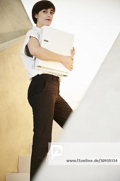 Frau mit Mappe und stehend auf der Treppe