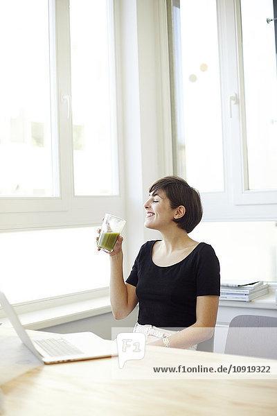 Glückliche Frau trinkt grünen Smoothie im Büro