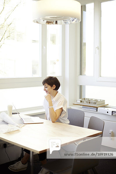 Architektin mit Laptop im Büro