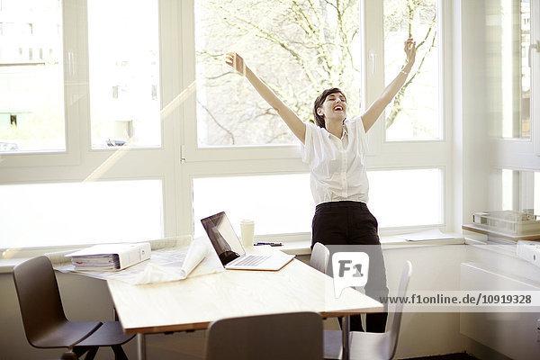Lachende Frau beim Stretching in ihrem Büro