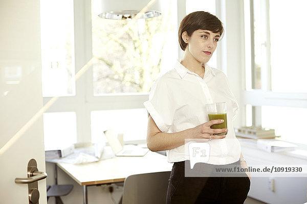Tagträumende Frau mit einem Glas grünen Smoothie im Büro