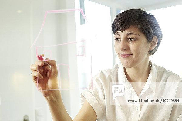 Porträt einer Frau,  die ein Haus auf einer Glasscheibe in einem Büro zeichnet.
