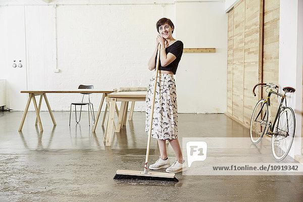 Lächelnde Frau mit Besen im Atelier
