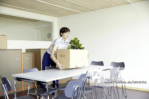 Lächelnde Frau mit Pappkarton im neuen Büro