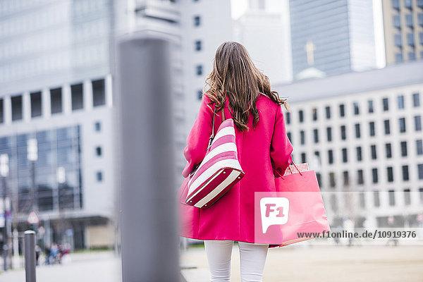 Junge Frau mit Einkaufstaschen in der Stadt  Rückansicht
