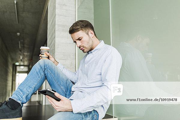 Junger Mann auf dem Boden sitzend mit digitalem Tablett