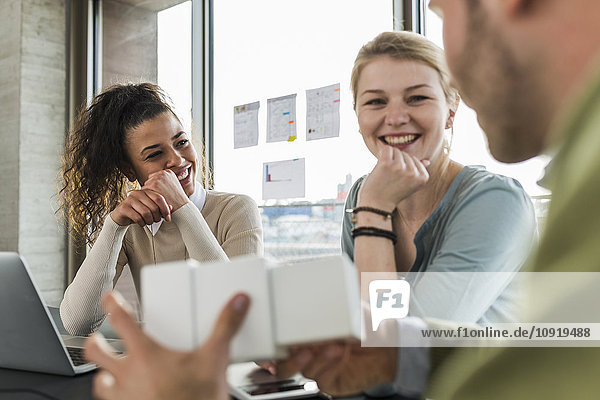 Three smiling colleagues in office working together