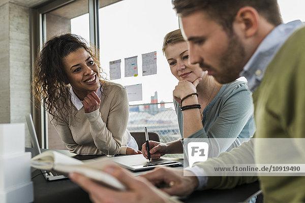 Drei Kollegen im Büro arbeiten zusammen