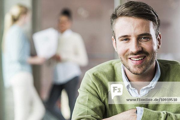 Porträt eines lächelnden jungen Mannes im Amt