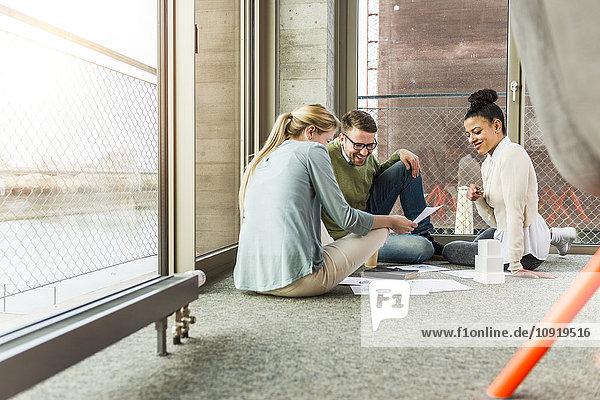 Drei Kollegen im Büro sitzen auf dem Boden und arbeiten zusammen.