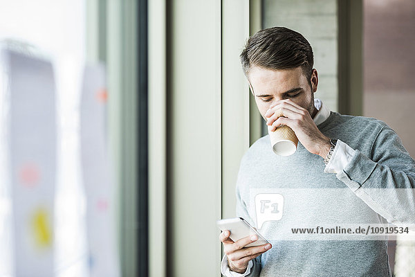 Young man with coffee to go looking at cell phone