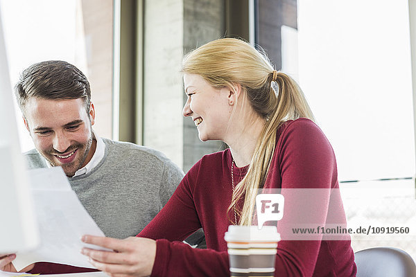 Two smiling colleagues looking at paper in office