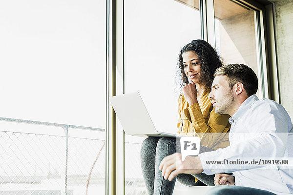 Zwei Kollegen im Büro mit Laptop