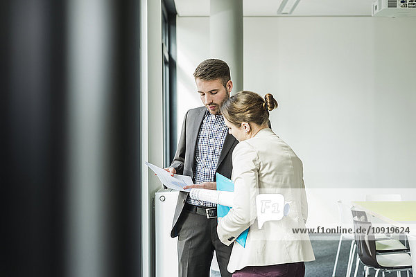 Zwei Kollegen diskutieren über Papier im Büro