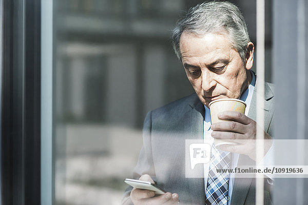Senior Geschäftsmann mit Kaffee zum Suchen auf dem Handy