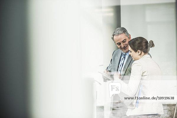 Senior Geschäftsmann und junge Geschäftsfrau teilen sich das digitale Tablett