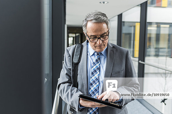Senior Geschäftsmann mit digitalem Tablett