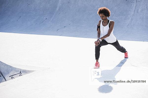 Junge Frau beim Stretching im Skatepark