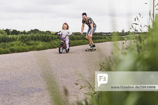 Vater auf dem Skateboard begleitet Tochter auf dem Fahrrad