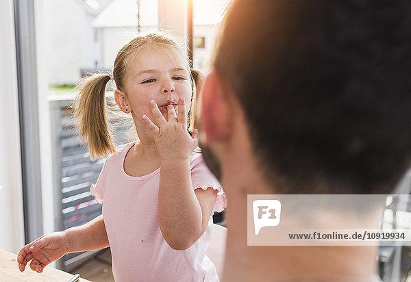 Mädchen mit Finger im Mund schaut Vater an