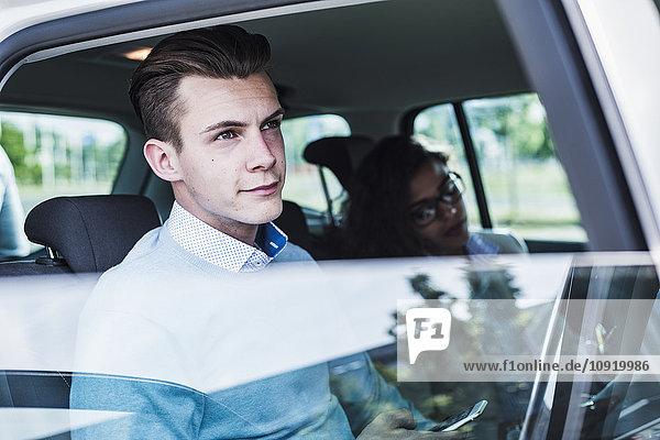 Junger Mann mit Handy und Frau im Auto