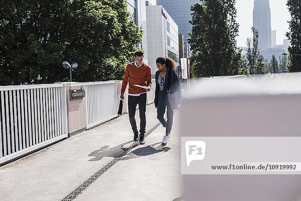 Junger Mann und junge Frau diskutieren Dokument im Freien