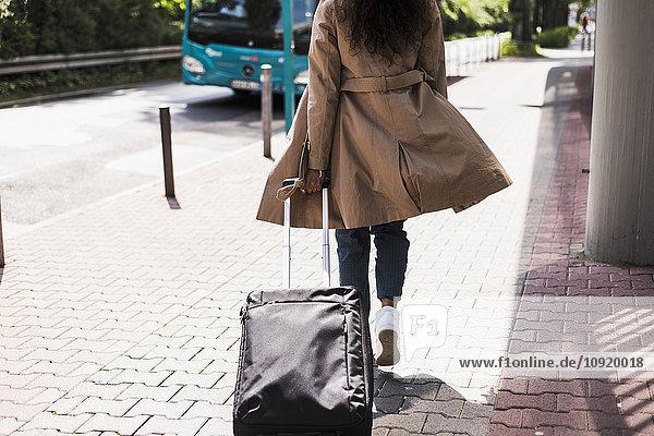Junge Frau mit Gepäck an der Bushaltestelle