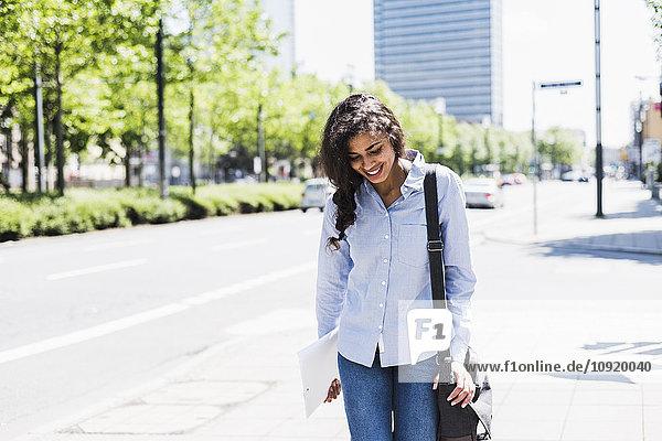 Lächelnde junge Frau unterwegs in der Stadt