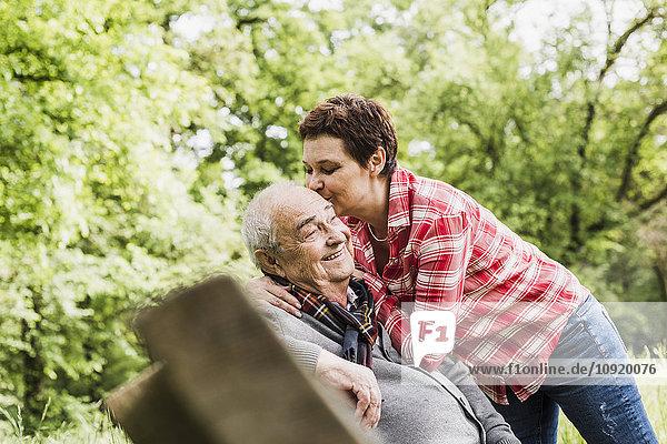 Glückliche Frau küsst ihren alten Vater auf einer Bank in der Natur.