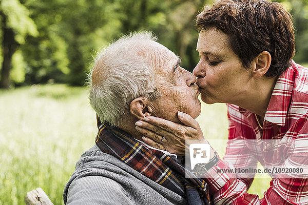 Frau küsst ihren alten Vater auf einer Bank in der Natur.