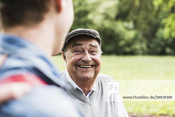 Porträt eines älteren Mannes im Gespräch mit seinem Enkel