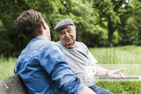 Porträt eines älteren Mannes  der auf einer Bank sitzt und mit seinem Enkel spricht.