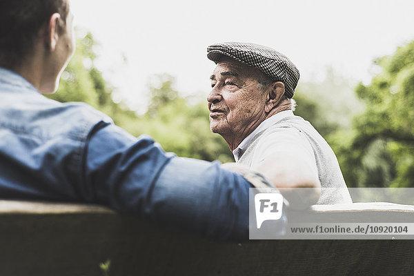 Porträt eines älteren Mannes im Gespräch mit seinem Enkel auf einer Bank