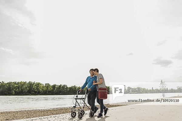 Älterer Mann  der mit Tochter am Flussufer spazieren geht