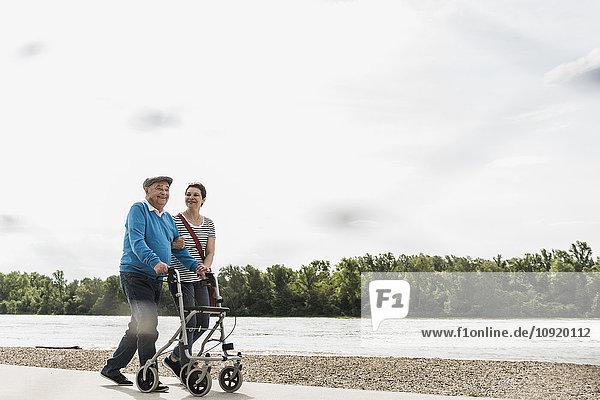 Ein älterer Mann  der mit seiner Tochter am Flussufer spazieren geht.