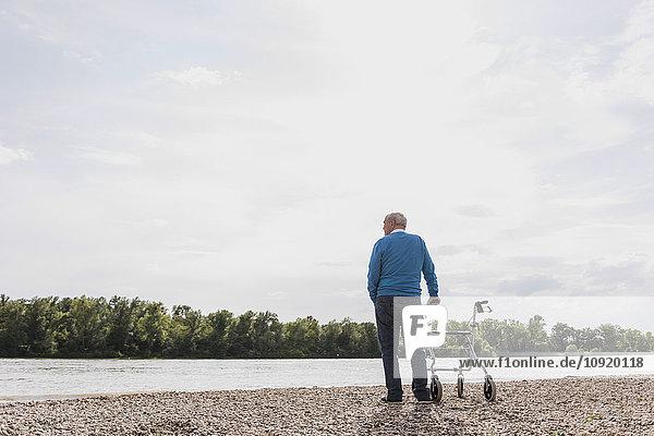 Rückansicht eines älteren Mannes mit Radwanderer am Flussufer
