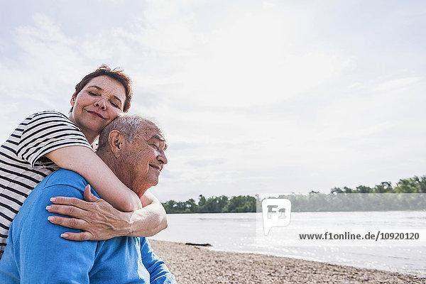 Erwachsene Tochter umarmt ihren Vater am Flussufer